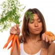 Woman holding bunch of fresh carrots and roll — Stock Photo