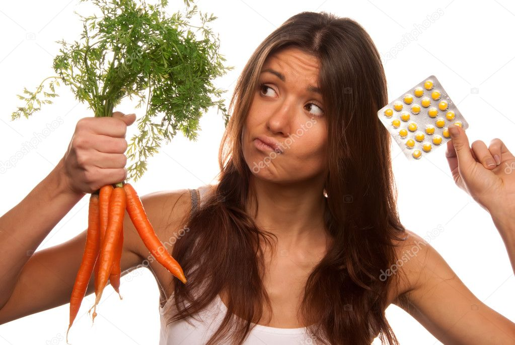 Young beautiful woman thinks deeply and making decision between organic fresh carrots and medical tablets to make the right choice and have no doubts. Most popu — Stock Photo #4749363