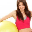 Slim female fitness instructor holds pilates ball in gym — Stock Photo #4892569