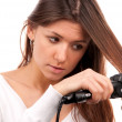 Woman using hair straighteners black flat iron — Stock Photo