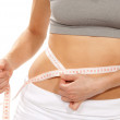 Athletic fit slim female measuring her waist — Stock Photo #5011121