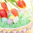 Easter spring eggs in basket and tulip flowers — Stock Photo