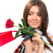 Woman with shopping bags and single red rose — Stock Photo #5178628