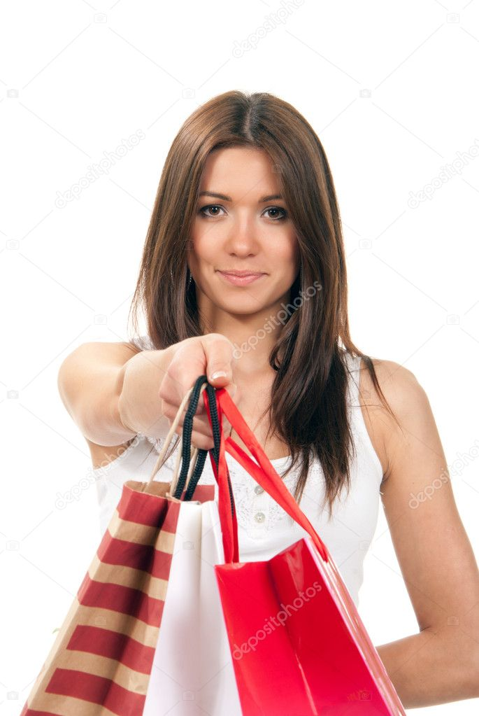 Young attractive cheerful smiling girl holding offer colored paper shopping bags in hand and giving them to the camera on a white background. Focus on face — Stock Photo #5253401