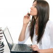 Woman sitting with laptop with pen in hand — Stock Photo