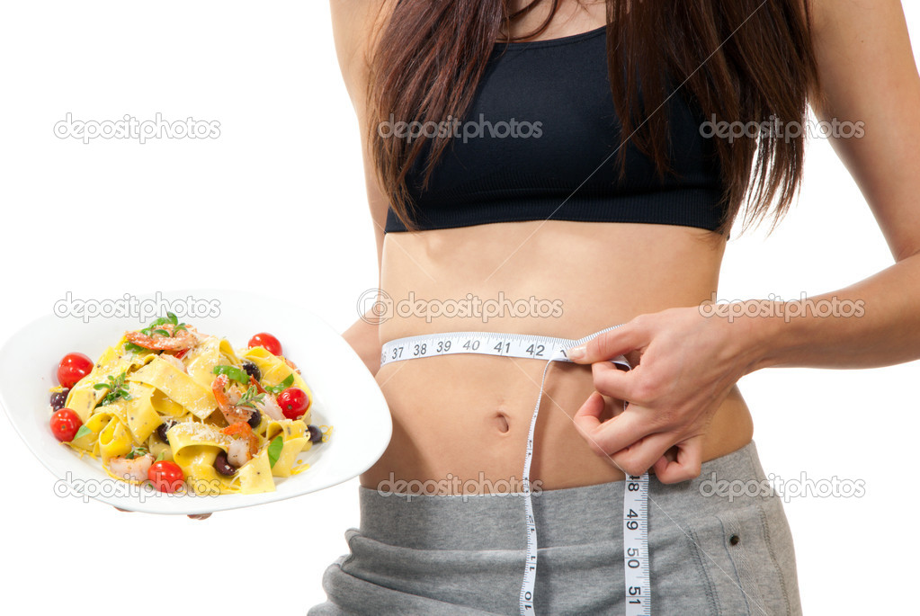 Young healthy slim girl measuring her waist with yellow tape measure, holding white plate with pappardelli, tagliatelli pasta, tomatoes, herbs, cheese on it , i — Stock Photo #5346406