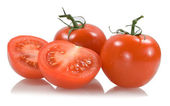 Red tomatoes with two tomato segments — Stock Photo