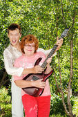 The guy of sixteen years with an electroguitar and the grandmother — Stock Photo