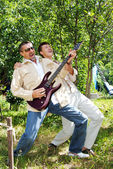 The man and the guy on the nature in the summer with an electroguitar — Stock Photo