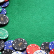 Poker chips on green felt poker table - Stock Photo