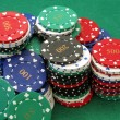 A stack of poker chips on green felt — Stock Photo