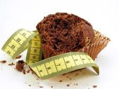Chocolate muffin with measuring tape — Stock Photo