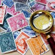 Stamps & magnifying glass — Stock Photo