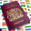 A British passport lying on a page of country flags - Stock Photo