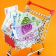 Euro currency in a shopping trolley on an orange background — Stock Photo