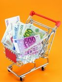 Euro currency in a shopping trolley on an orange background — Foto Stock