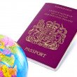 A passport next to a globe — Stock Photo