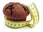 Chocolate muffin & measuring tape — Stock Photo