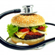 Cheesesburger & stethoscope on white background — Stock Photo