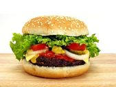 Cheeseburger on wooden board — Stock Photo