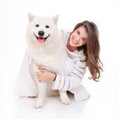 笑みを浮かべて白い犬を持つ女性 — ストック写真