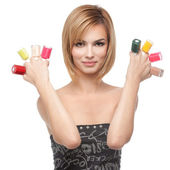 Young woman showing eight bottles of nail polish — Stock Photo