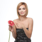 Portrait of a young woman picking pettals from a flower, looking — Stock Photo