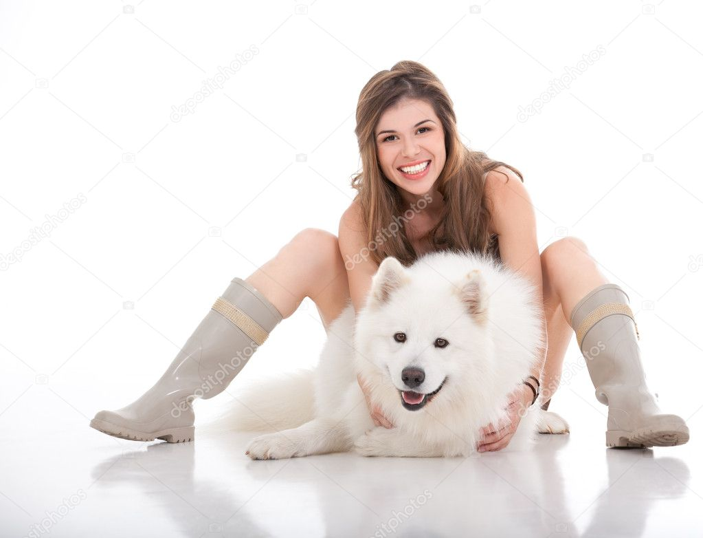 A studio image of a young woman hugging her white dog, which she holds in front of her, looking forward and smiling. — Stock Photo #4371346