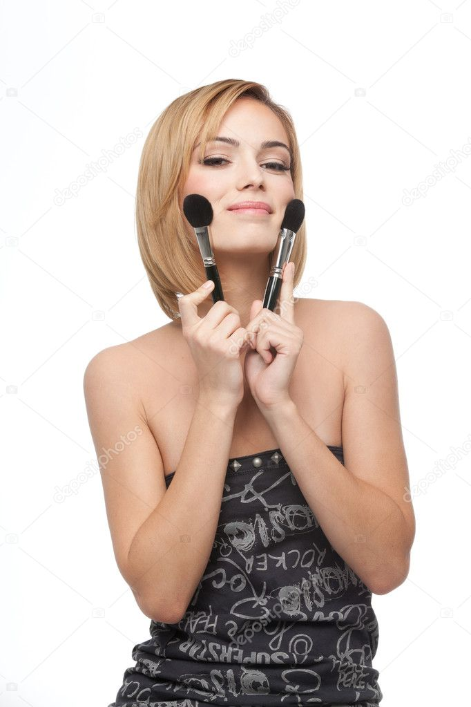 A portrait of a young, blonde woman, holding a make-up brush in each hand, appling blush — Stock Photo #4371570