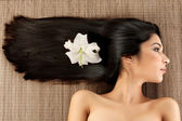 Profile spa portrait of a young woman with a lilly flower in her — Stock Photo