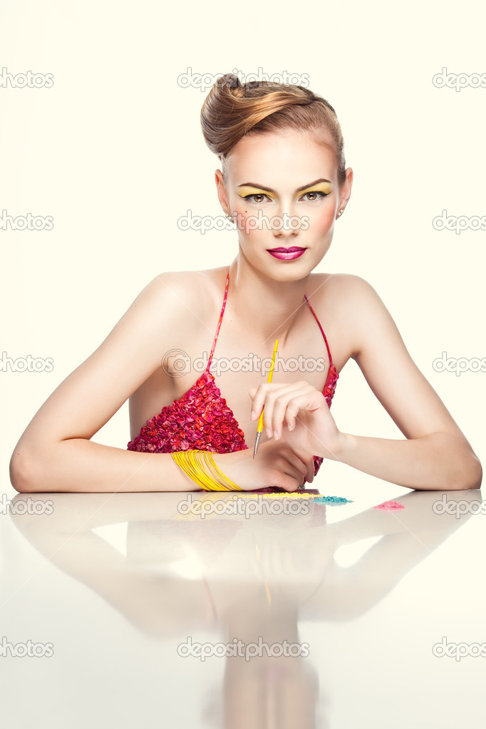 A studio beauty portrait of a young woman, with colorful makeup and clothes, shot on white background. She holds a makeup brush in one hand as she is trying on  — Stock Photo #4931016