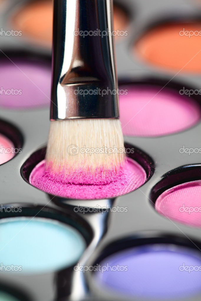 A close-up image of a eye-shadow kit, with a professional makeup brush picking up some pink colour — Stock Photo #5053506