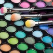 图库照片: Eyeshadow kit with three makeup brushes