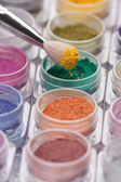 Cosmetic brush pigment above containers of pigments — Stock Photo