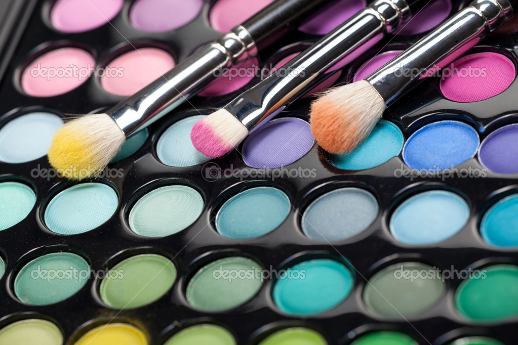 A close-up image of a eye-shadow set, with three professional makeup brushes with different pigment on them — Foto Stock #5240132