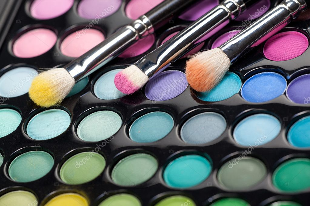 A close-up image of a eye-shadow set, with three professional makeup brushes with different pigment on them — Photo #5240132