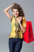 Jonge vrouw in kleurrijke outfit die een rode shopping tas, smil — Stockfoto