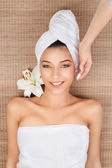 Portrait of young woman at a spa, lying on her back, smiling, wi — Stock Photo