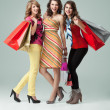 Studio image three beautiful young women holding shopping bags s — Stock Photo