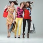 Studio image three beautiful young women holding shopping bags w — Stock Photo