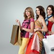 Studio image three beautiful young women holding shopping bags s — Stock Photo #5342212
