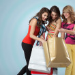 Studio image three beautiful young women holding shopping bags l — Stock Photo