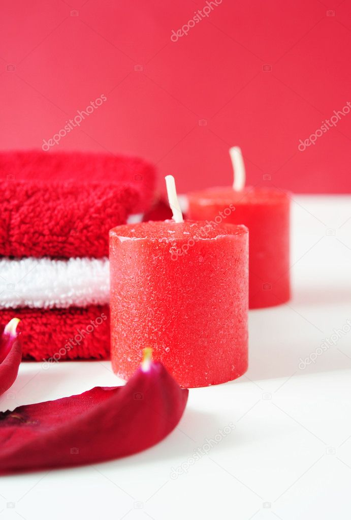 A tower of white and red towels, rose petals and red candles — Stock Photo #5079425
