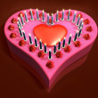 3d lit candle on red heart cake — Stock Photo