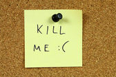Yellow sticky note pinned to an office notice board. Kill me - suicidal, depression message. Euthanasia concept. — Fotografia Stock