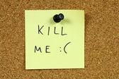 Nota auto-adesiva amarela pregada a um quadro de avisos do escritório. mate-me - suicida, depressão mensagem. conceito de eutanásia. — Foto Stock