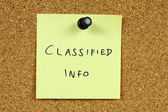 Yellow sticky note pinned to an office notice board. Classified info - secred government information concept. — Stock Photo