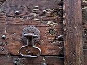 Wooden door, knocker and keyholes — Stock Photo