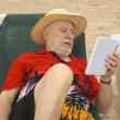 Senior reader on the beach — Stock Photo