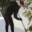 Stock Photo: Young woman shovelling snow